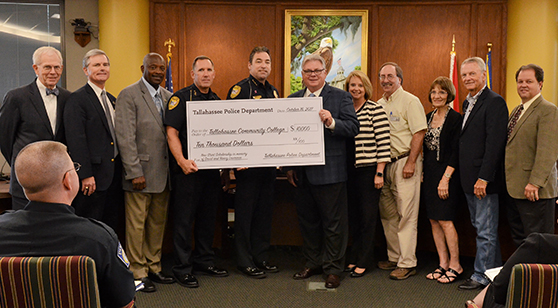 Police department and TCC officials with big check