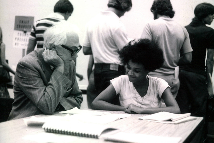 Founding TCC President Fred Turner sits at table with a black, female student reviewing her transcript during registration