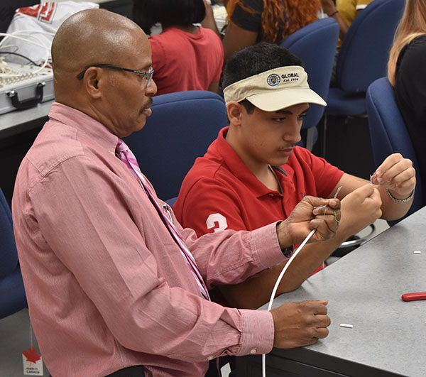 Instructor helps student with cabling