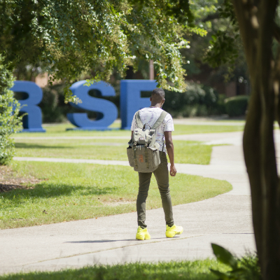 A student walks past the large R-I-S-E letters as part of the Foundation's RISE campaign