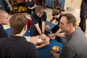 Students performing CPR with instructor supervision