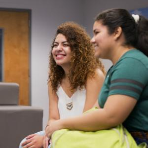 Two girls smile at group discussion in honors lounge