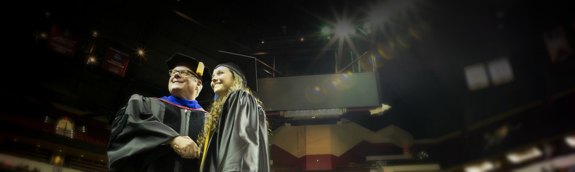 A graduate shakes hands with the President while posing for a picture at commencement