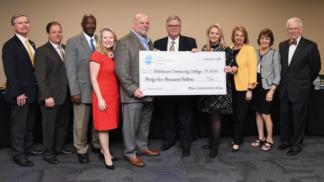 Moore Communications Group and TCC officials hold big check